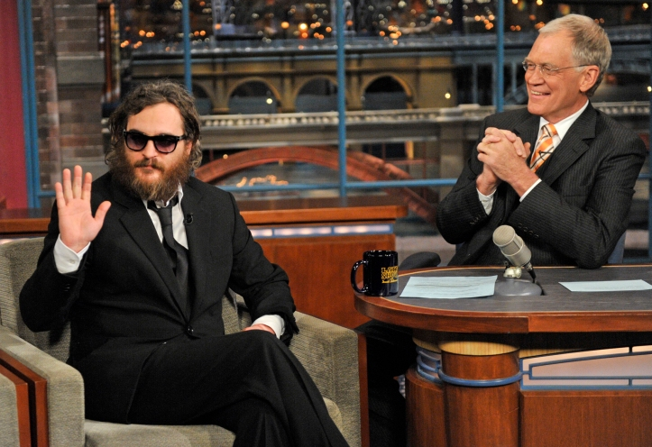 In this photo released by CBS, actor Joaquin Phoenix, left, waives to the audience from the set of the